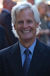 A man with white hair is looking and smiling at the camera.