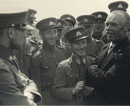 "Soviet political leader (without military shoulder straps) and the marionette People's Seimas member (with red rose in his jacket lapel) announces to the Lithuanian People's Army non-commissioned officers that ""soon you will become members of the Red Army"" in Kaunas, 1940 Communists with the Lithuanian Army soldiers.jpg"