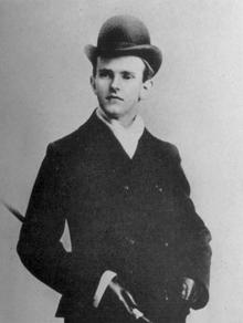 Photographie d'un jeune homme portant une veste, un chapeau et une cane