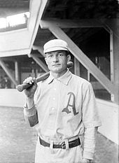 "A man wearing an old-style white baseball uniform with a large script ""A"" over the left breast and holding a baseball bat over his right shoulder"
