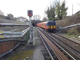 "Shepperton branch line - Train in the railway cutting at Fulwell approaching the station. The ""tunnel"" is actually an overbridge."