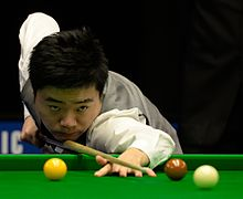 Ding looks down his cue and prepares to take a shot.