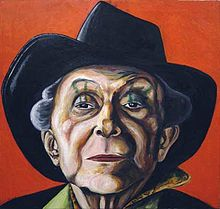 This colorful portrait focuses on Crisp's face (under his trademark fedora), but the viewer can still glimpse a stylish shirt collar. Crisp squints down his nose at the viewer through almond-shaped eyes. Green stripes extend from eyelid to eyebrow.
