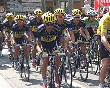 A group of cyclists wearing blue and yellow clothing.