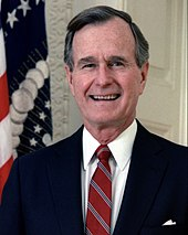 Official portrait of George H. W. Bush standing in front of an American flag