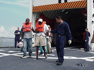 Repatriation - Haitian migrants are escorted off the Coast Guard Cutter Tampa's fantail to an awaiting Haitian Coast Guard vessel during repatriation