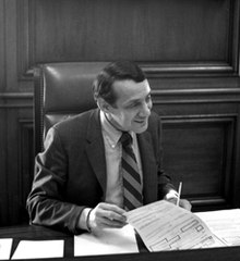 A black and white photograph of Harvey Milk sitting at the mayor's desk