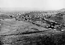 B&W photograph of a sprawling town of wooden buildings in a valley