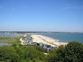 view looking down from a hill onto a sandy shoreline