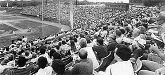 A black and white photograph of a baseball game in progress with fans looking on and few empty seats in sight