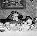 Holger Bandmann zit aan een tafel gedekt met koffieservies en gebak, Bestanddeelnr 254-3355.jpg