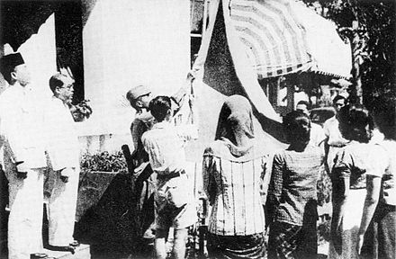 Bendera Pusaka, the first Indonesian flag, is raised on 17 August 1945. Indonesian flag raised 17 August 1945.jpg