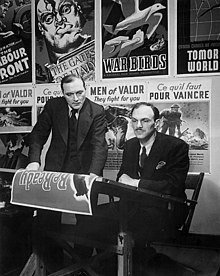 Two men looking at a film poster on a desk against a background of movie posters