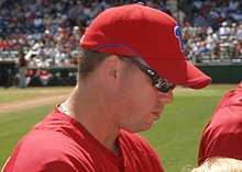 A man in profile, wearing a red baseball jersey and red baseball cap