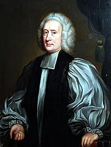 A middle-aged white man seated and wearing Georgian-era English clerical robes.