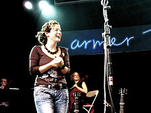 A woman with curly brown hair stands near a microphone stand, wearing a brown T-shirt and jeans.  The necks of two guitars are visible beside the microphone stand.  In the background are two more women, one of whom is holding a cello.