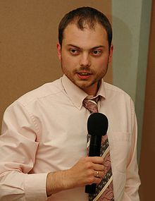 A standing bearded Russian man while wearing a pink shirt and striped necktie while holding a wireless black microphone; on his right index finger is a shiny golden wedding ring.