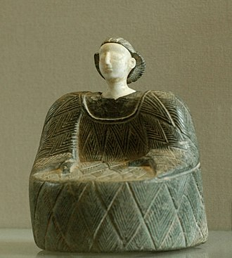 Female statuette wearing the kaunakes. Chlorite and limestone, Bactria, beginning of the 2nd millennium BC. Kaunakes Bactria Louvre AO31917.jpg