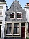 foto van Pand van middeleeuwse oorsprong, thans voorzien van een ingezwenkte halsgevel uit de eerste helft van de 19e eeuw, bestaande uit twee bouwlagen met kap loodrecht op de straat
