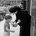 Little boy putting money in nun's collection tray (32348387582).jpg