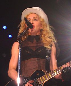 Picture of a middle-aged blond woman uptill the waist, singing in front of a microphone. Her hair is in waves and falls up to her shoulders. She appears to be wearing a black bra covered with a sleeveless netted covering and wears a white hat on her head. There are black gloves on her hand and she plays an electric guitar.