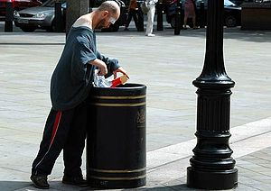 A man finding stuff to eat in a bin in London.