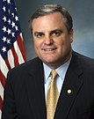 Mark Pryor, head and shoulders photo portrait with flag, 2006.jpg