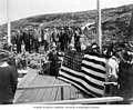 Members of the Seattle Chamber of Commerce raising the United States flag at the border between Alaska and Canada, ca 1914 (CURTIS 1881).jpeg