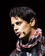 A photo of Milo Yiannopoulos at the LeWeb13 Conference in Paris, France, wearing a microphone headset and a red, black, and white scarf over a brown leather jacket