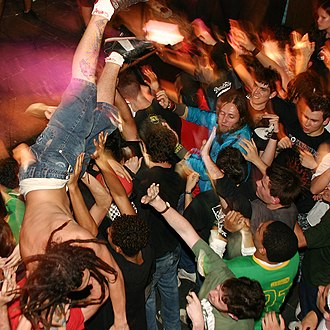Moshing - Crowdsurfing over a mosh pit.
