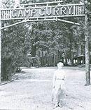 """Virino en longa robo antaŭ signo trans vojo. Lignaj leteroj legas """"Camp Curry""""."""
