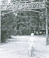 "Woman in a dress in front of a sign above a road made of wood lettering. The sign reads ""Camp Curry"" and trees are in the background."