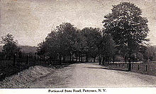 "A black and white illustration of an unpaved highway flanked on both sides by fence and trees proceeds through mostly open land. A caption at the bottom reads ""Picture of State Road, Patterson, N.Y."""