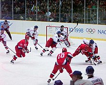 A hockey game between two teams; one is wearing red uniforms, and the other has white jerseys, red pants, and blue helmets.