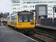 An orange painted train with two carriages leaving a railway platform.