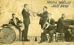 "1918 promotional postcard of the ODJB showing (from left), drummer Tony Sbarbaro (aka Tony Spargo), trombonist Edwin ""Daddy"" Edwards, cornetist Dominick James ""Nick"" LaRocca, clarinetist Larry Shields, and pianist Henry Ragas"