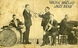 A jazz band playing: A drummer on the left behind a drum set, a trombonist next to him facing right. A cornetist standing behind the trombonist facing left, and a clarinetist sitting on a chair in the front. A pianist sitting on the far left, facing right.