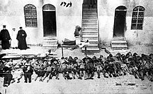 Photograph of corpses lined up on the street. Orthodox clergy stand by.