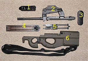 FN P90 - A disassembled PS90 carbine, showing the major component groups. The standard P90 disassembles into similar component groups: 1. hammer group, 2. barrel and optical sight group, 3. butt plate, 4. magazine, 5. moving parts group, 6. frame and trigger group