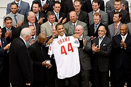 "Several rows of men standing and clapping; in the front is a smiling, brown-skinned man holding a white baseball jersey with ""Obama"" and a large ""44"" in red on the rear toward camera"