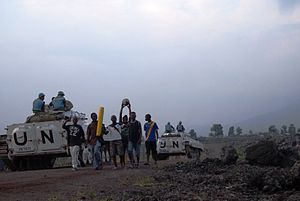 Kivu conflict - MONUSCO peacekeepers of the North Kivu brigade on patrol in a street of Goma pass a group of teenagers returning from a football game.