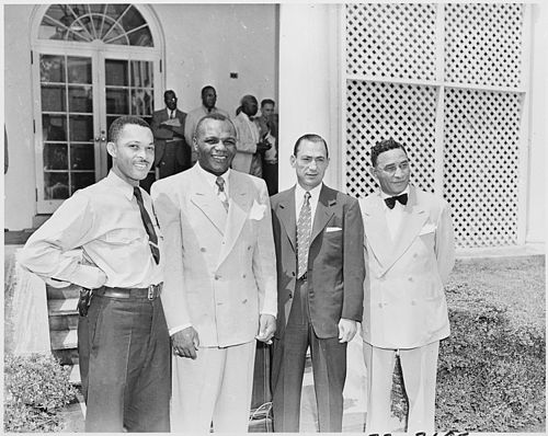 Photograph of Jersey Joe Walcott, the heavyweight champion of the world (second from left), with three other persons... - NARA - 200324.jpg