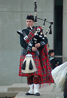 Full plaid long length of tartan fabric pleated and wrapped around the body, worn with a sewn kilt, as part of Scottish highland dress
