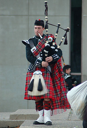 Full plaid - A bagpiper and member of the Queen's Bands wearing a full plaid in traditional highland dress.