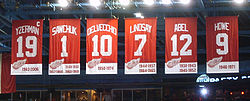 A row of six large red banners with white letters and numbers.  The banners read, from left to right − YZERMAN 19 − SAWCHUK 1 − DELVECCHIO 10 − LINDSAY 7 − ABEL 12 − HOWE 9
