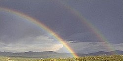 A double rainbow features reversed colours in the outer (secondary) bow, with the dark Alexander's band between the bows.