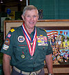 man in Venturer uniform with medals, painting in background