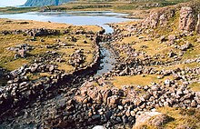 A stone lined ditch of primitive construction leads from a small lake. Rocky heathland lies on either side and there are tall cliffs in the distance.
