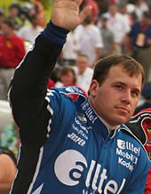 A man in his early thirties wearing a blue jacket with sponsors' logos. His right arm and hand are elevated in a waving gesture.