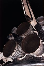 Three bell-shaped rocket engine nozzles projecting from the aft structure of a Space Shuttle orbiter. The cluster is arranged triangularly, with one engine at the top and two below. Two smaller nozzles are visible to the left and right of the top engine, and the orbiter's tail fin projects upwards toward the top of the image. In the background is the night sky and items of purging equipment.